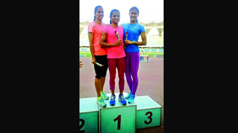Sprinter Dutee Chand (centre) is all smiles as she poses with second placed Merline Joseph and bronze medallist Himanshi Roy at the Indian Grand Prix at the Jawaharlal Nehru Stadium in New Delhi on Monday.