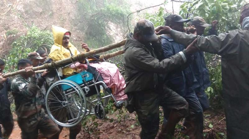 Soldiers shifting a flood victim to a safe place at Allekahan Horate village in Mudigere taluk on Sunday (Photo: KPN)