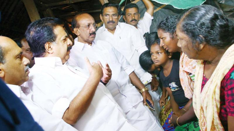 Opposition leader Ramesh Chennithala interacts with family members of farm workers who died due to exposure to pesticides, in Vengala on Monday.