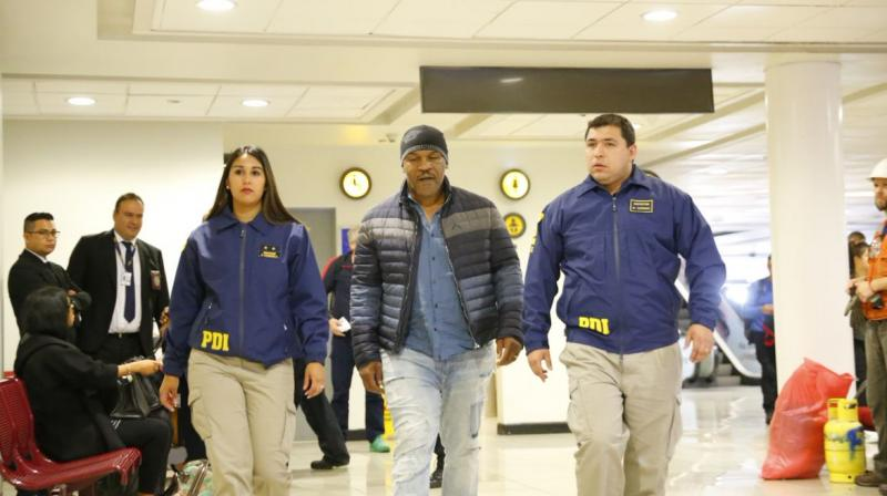 Mike Tyson being being escorted by officers at Santiago international airport for 'not complying with immigration law'. (Photo: Twitter/PDI Chile‏)