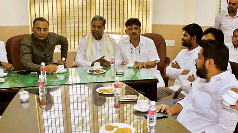 Senior Congress leaders Dinesh Gundurao, Siddaramaiah and D.K. Shivakumar at a party meeting in Bengaluru on Friday