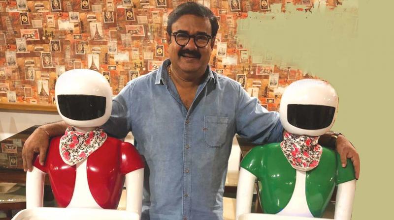 Maniyanpilla Raju posing with his two robots
