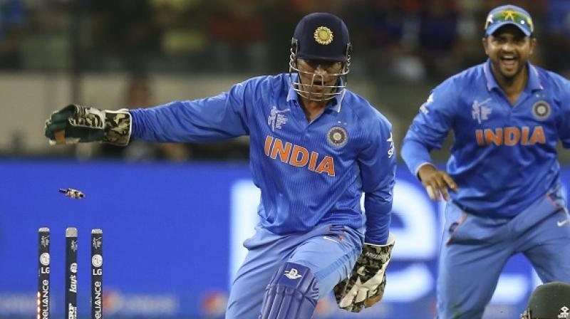 Mahendra Singh Dhoni, who was a special guest at the Sehwag International School, was seen giving batting and wicketkeeping tips to some of the students there. (Photo: AP)
