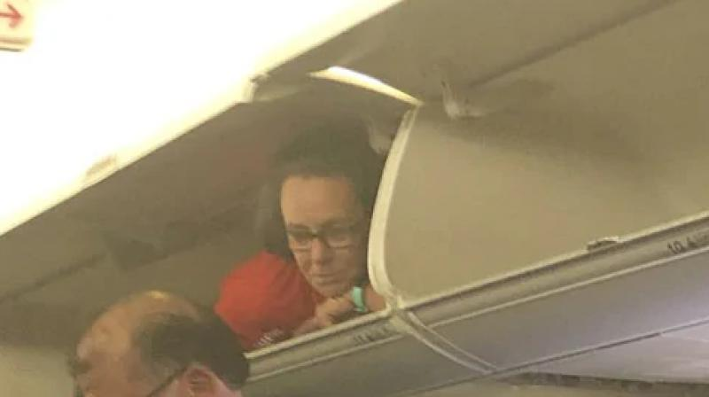 Southwest Airlines flight attendant climbs into overhead compartment