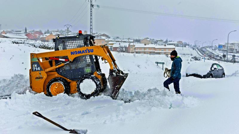 A small bulldozer clears a road at the entrance of Villacastin, Segovia province, after the winter's first heavy snowfall