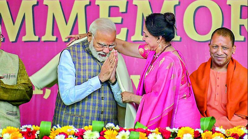 PM Narendra Modi being greeted with a shawl by the local BJP MP Hema Malini as CM Yogi Adityanath looks on in Vrindavan near Mathura, Monday. (PTI)