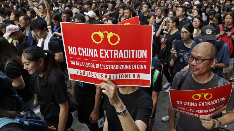 Protesters raise placards as they march on the streets against an extradition bill in Hong Kong on Sunday, June 16, 2019. (Photo: AP)