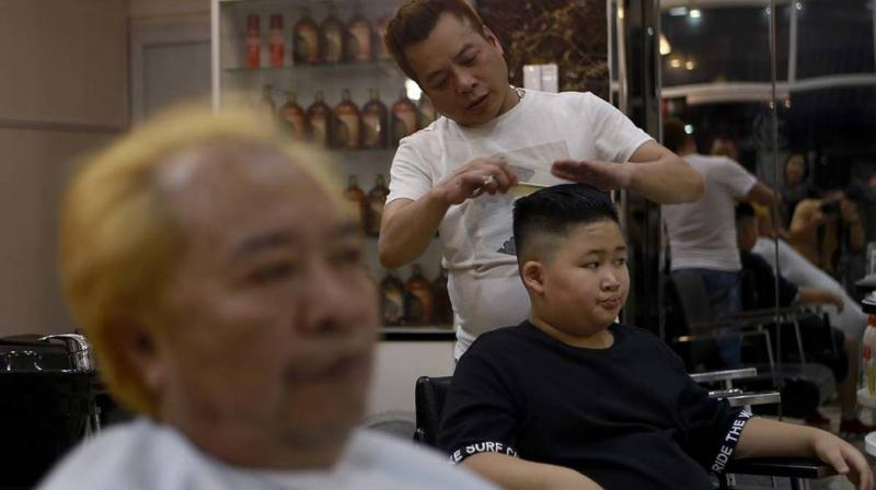 Barber Le Tuan Duong has been overrun with customers since word got out about his free dos, a gesture he's offering out of sheer excitement for the February 27-28 meeting in Hanoi. (Photo: AP)