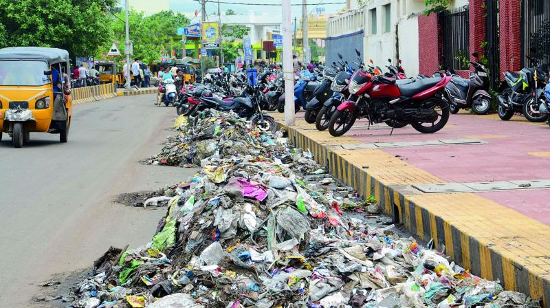 Vehicles are parked on the footpath as garbage is dumped on the road outside the Naval Canteen on the beach road in Visakhapatnam on Saturday. During the weekend and due to lack of parking space, vehicles are being parked on the road creating inconvenience to the people at this junction.
