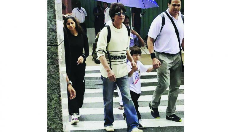 SRK held AbRam's hand as they walked out of the airport, while Aryan and Suhana walked behind them.