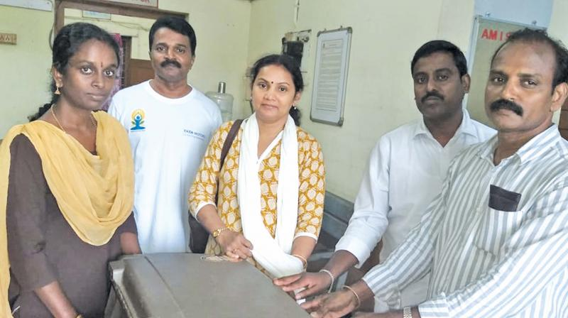D. R. Uma Maheswari (far left) travelling ticket examiner and N. Gurunathan (far right), travelling Ticket Inspector hand over the retreived suitcase to the passengers. (Photo: DC)