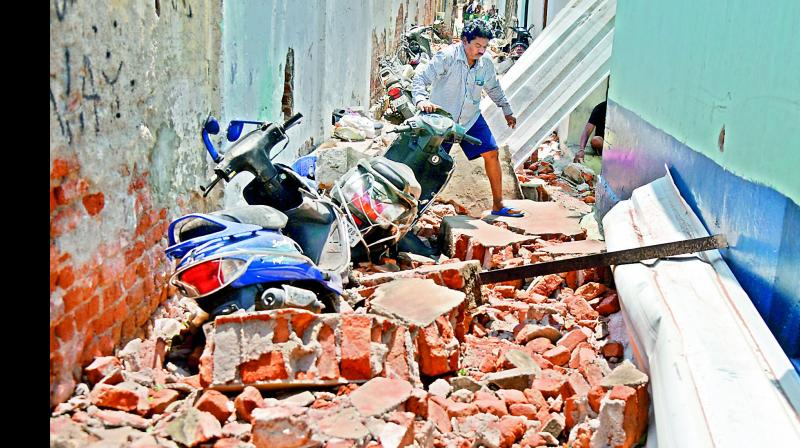 Above: A man tries to remove a scooter partially buried under the debris of a wall that collapsed near the Old Gandhi Hospital on Monday.  Right: The spire of one of the minarets of the Madannapet Idgah was damaged.  — DC