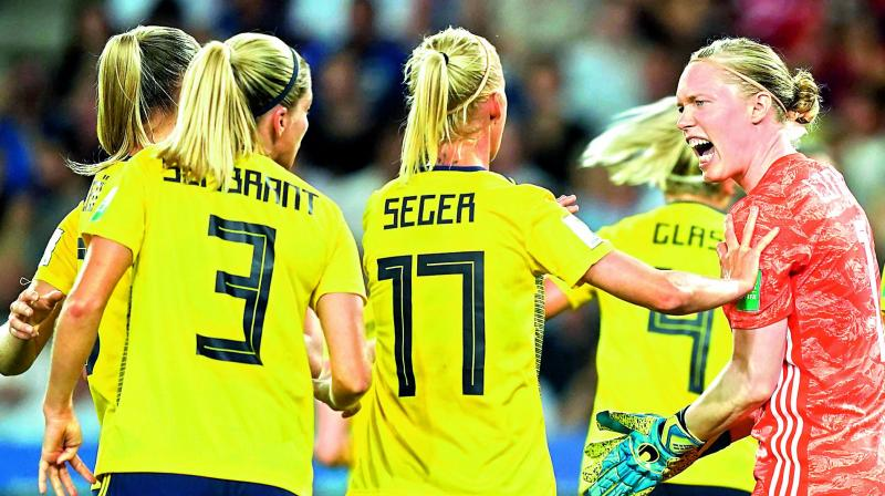 Sweden's goalkeeper Hedvig Lindahl (right) is congratulated by teammates after saving a penalty against Canada during the Women's World Cup pre-quarterfinal football match at the Parc des Princes stadium in Paris on Tuesday. (Photo: AFP)