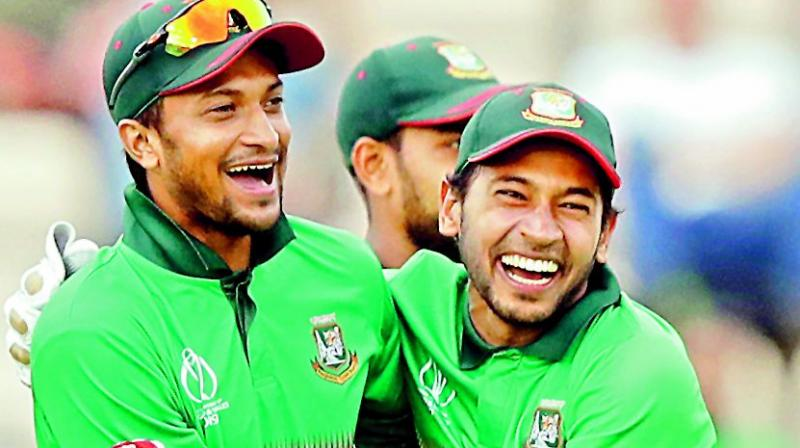 Bangladesh's Shakib Al Hasan (left) Mushfiqur Rahim celebrate after the wicket of Afghanistan's Rashid Khan in their group stage match at the Hampshire Bowl in Southampton on Monday. (Photo: AFP)