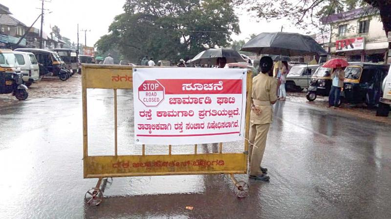 A road barricade asking people to take a diversion which was put up due to five landslides, at Ujjire, Belthangady Taluk, in the foothills of Charmadi Ghat on Wednesday  (Image: DC)