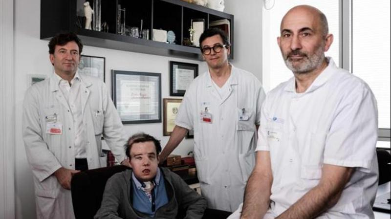 French medicine professor Laurent Lantieri (right), a specialist in hand and face transplant, poses with members of his team and his patient Jerome Hamon on April 13, 2018 at the Hopital Europeen Georges-Pompidou in Paris. (Photo: AFP)