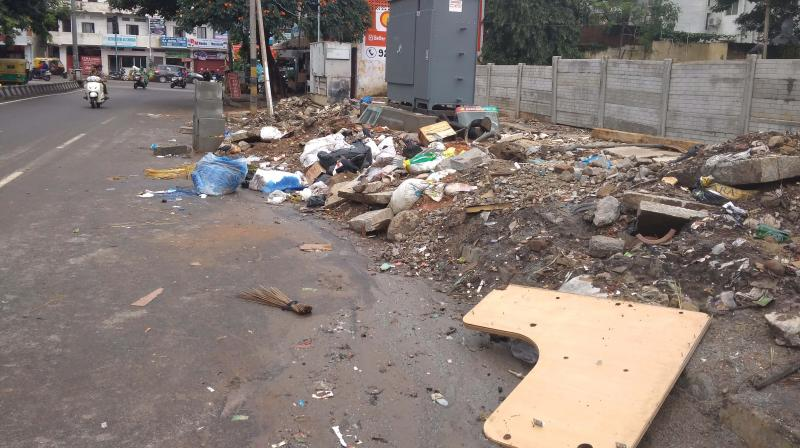 The footpath opposite at the East End Circle in Jayanagar has become a dumping ground for construction debri and garbage (Photo: R Samuel)