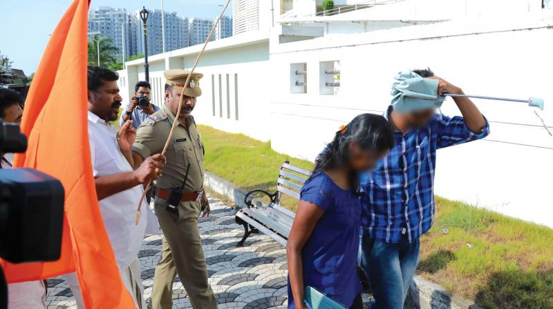 A Shiv Sena activist threatens to cane a couple even as Central Station sub-inspector Vijayashankar seems to be pleading with him to spare the duo at Marine Drive in Kochi on Wednesday. (Photo: ARUN CHANDRABOSE)