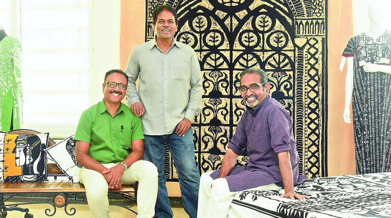 Manzoor Hussain, Sajid Bin Amar and A. Rajeswara Rao pose in front of a bedspread by Rao