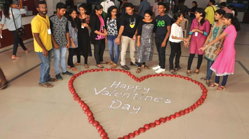 Students of Sacred Heart College, Thevara, celebrate the Valentine's Day on the campus by making the symbolic love sign with red coconut shells painted in blazing red.(Photo: SUNOJ NINAN MATHEW)