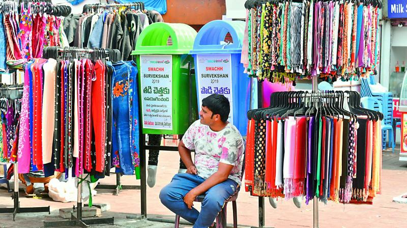 A hawker restricts access to GHMC's dustbins by setting his shop around the bins in front of the Charminar on Thursday. — Gandhi