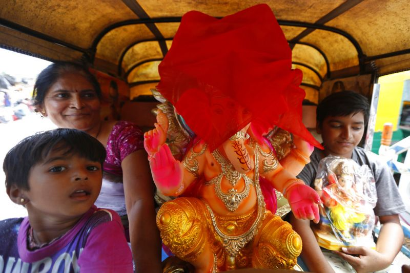 Devotees transport an idol of elephant-headed Hindu God Ganesha home in an auto for worship during Ganesh Chaturthi festival in Ahmadabad. (Photo: AP)