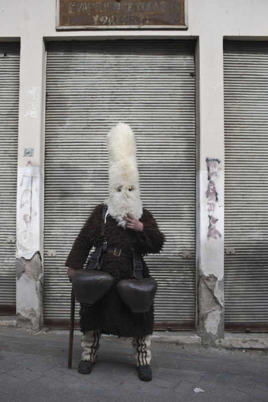 A man wearing a mask that includes a meter- tall, ribbon-covered formation topped with a foxtail. (Photo: AP)