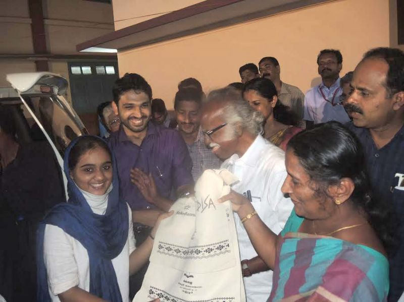 Minister Kadannappally Ramachnadran gifts cloth bag to a student on Friday night. District Collector Mir Mohammed Ali, District Panchayat President KV Sumesh, Mayor E.P Latha among others look on.(Photo: DC)