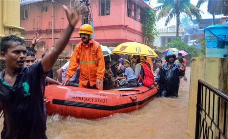 Rescuers shift people to a safer place from a flooded locality, after a thunderstorm, in Mangaluru. (Photo: PTI)