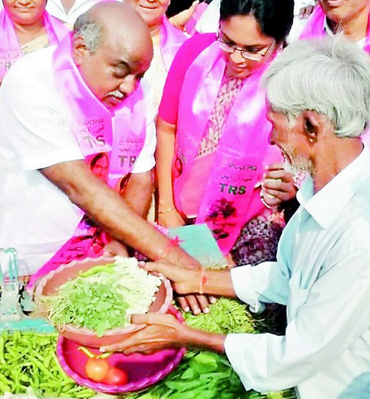 Caretaker minister Jogu Ramanna sells vegetables as part of his campaign in Adilabad on Tuesday. (Photo: DC)