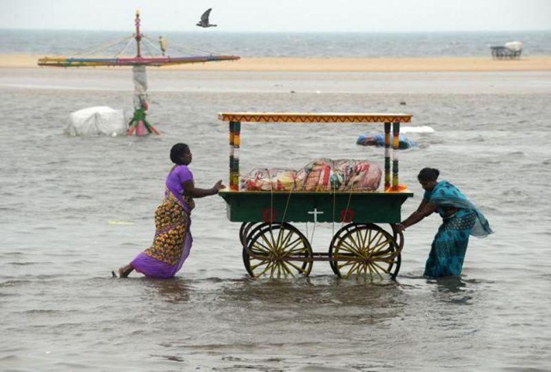 Two women push a food cart through flood waters at Marina Beach on the Bay of Bengal coast, Chennai. (Photo: AFP)