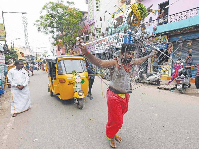 A body pierced  devotee in Thulukanathamman temple in Triplicane pulls an auto as part of Aadi festivities. (Photo: DC)