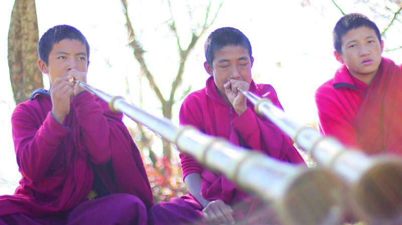 Young monks playing the tung chen at Chimi Lakhang temple
