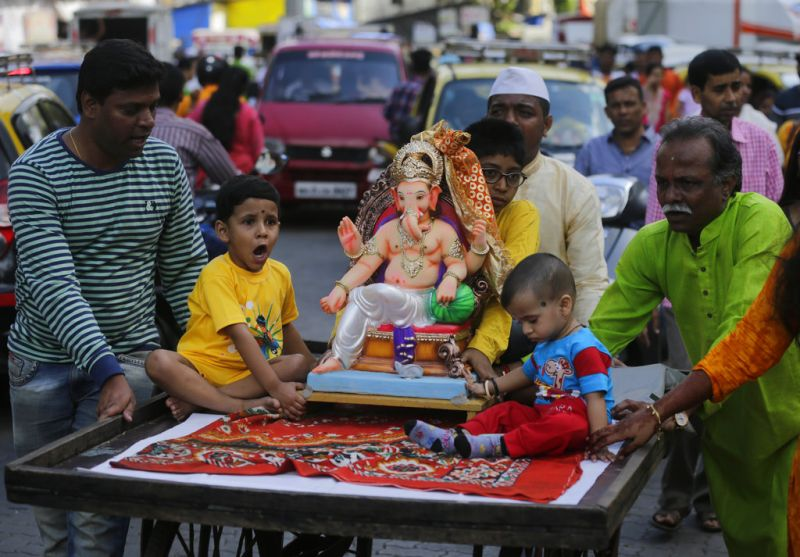 Devotees carry a Ganesh idol home on a cycle-rickshaw for worship during Ganesh Chaturthi festival celebrations in Mumbai. (Photo: AP)