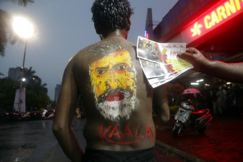 A man with the face of superstar Rajinikanth painted on his back poses for a picture outside a cinema hall before watching Rajinikanth's new movie 'Kaala' in Mumbai. (Photo: AP)