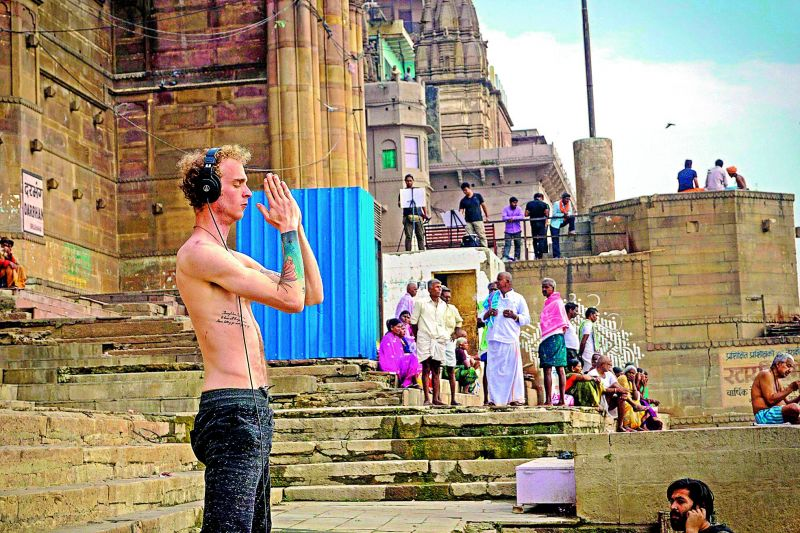 A foreign tourist listens to music while praying on the ghats of Varanasi.