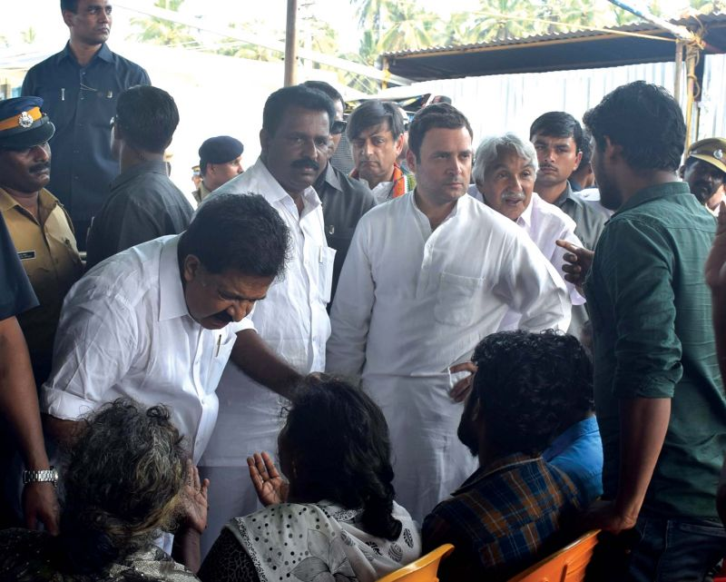 Congress president Rahul Gandhi and Opposition leader Ramesh Chennithala interact with the victims of Cyclone Ockhi in Thiruvananthapuram. (Photo: DC FILE)