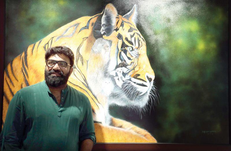 Kottayam Nazeer with his paintings at Durbar Hall Art Centre