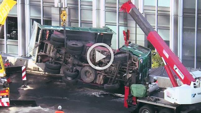 Driver killed as dump truck rolls over and dangles on Tokyo highway