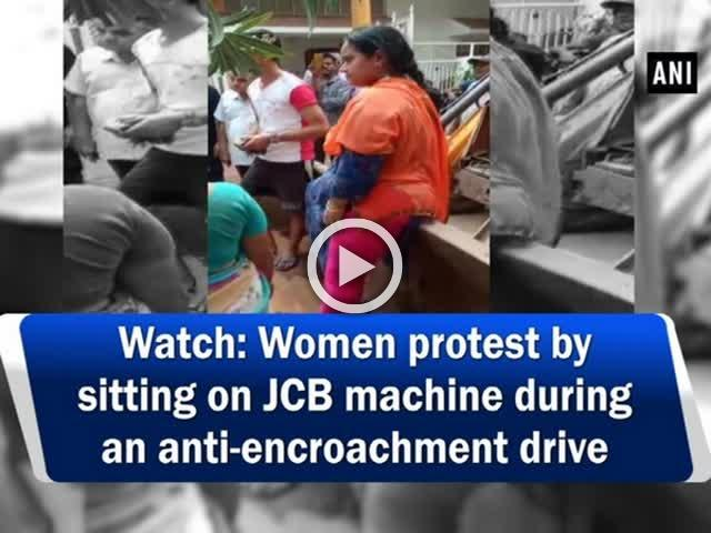 Watch: Women protest by sitting on JCB machine during an anti-encroachment drive