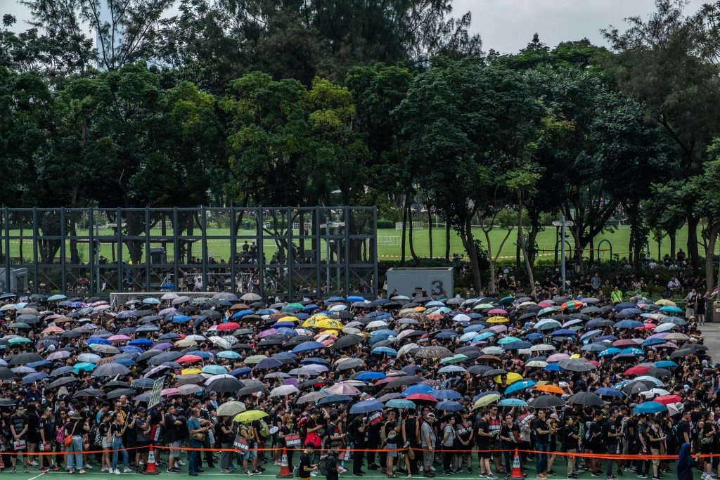 Marchers wait in Victoria Park with umbrellas