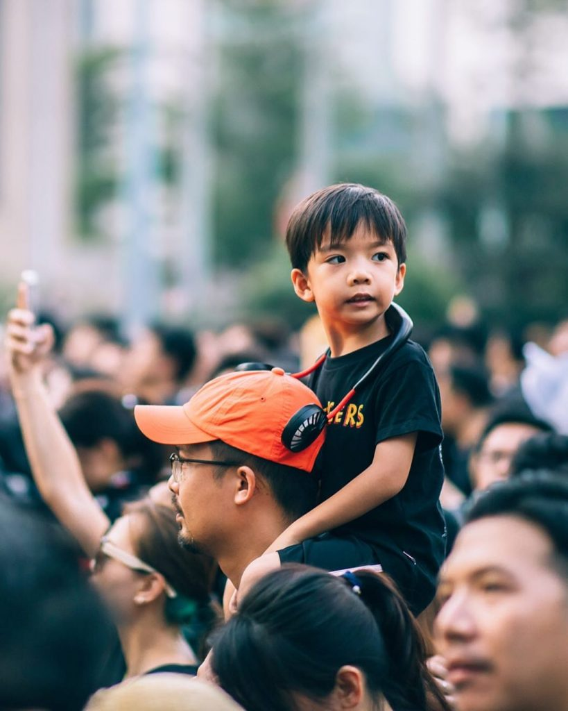 Child on his father's shoulders overlooking the protest