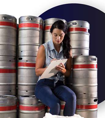Woman writing on notepad while sitting on kegs