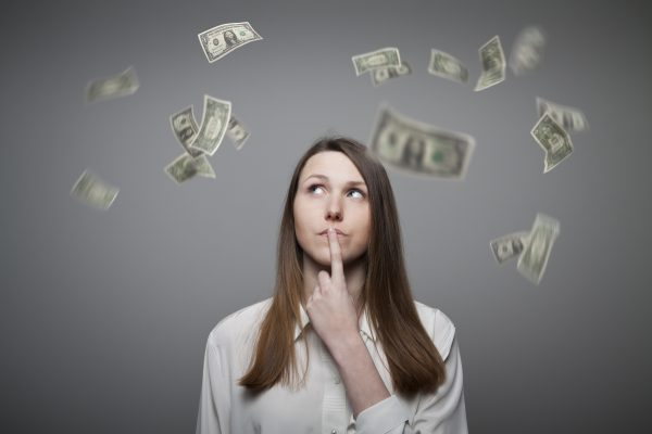 Girl in white and falling dollar banknotes. Currency and lottery concept. Young woman is thinking.
