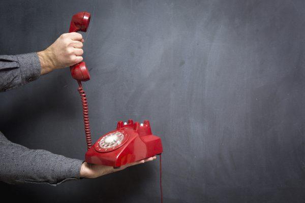 Human hand holding telephone on blackboard - Contact Us.
