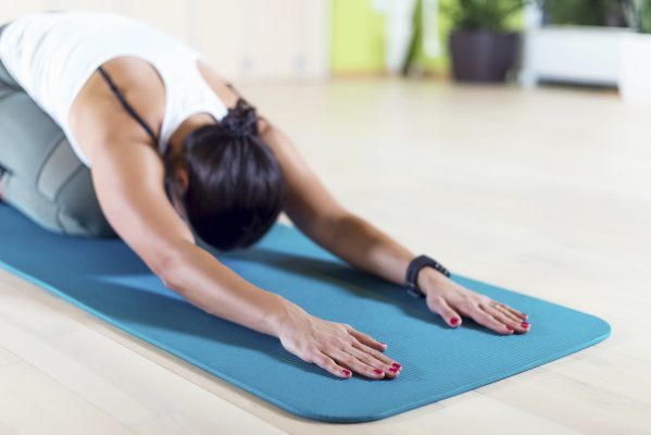 Fit woman doing stretching pilates exercises in fitness studio