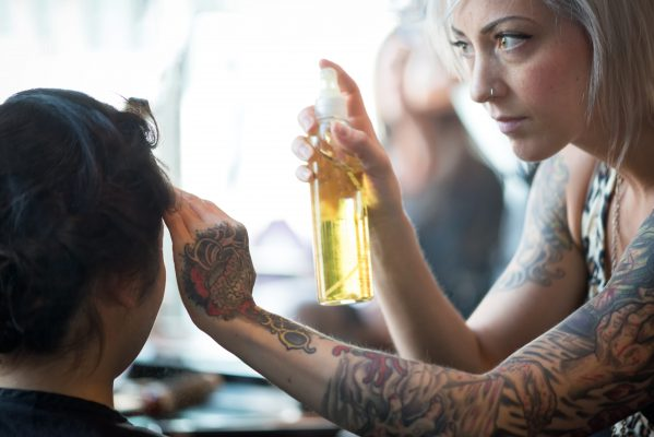 A serious, attractive young woman hair stylist with unique style (tattoos, piercings, platinum hair, leopard skin clothing) uses hairspray to complete a client's hairstyle – a trendy, braided updo for high school formal (graduation). Salon in Vancouver, British Columbia, Canada.