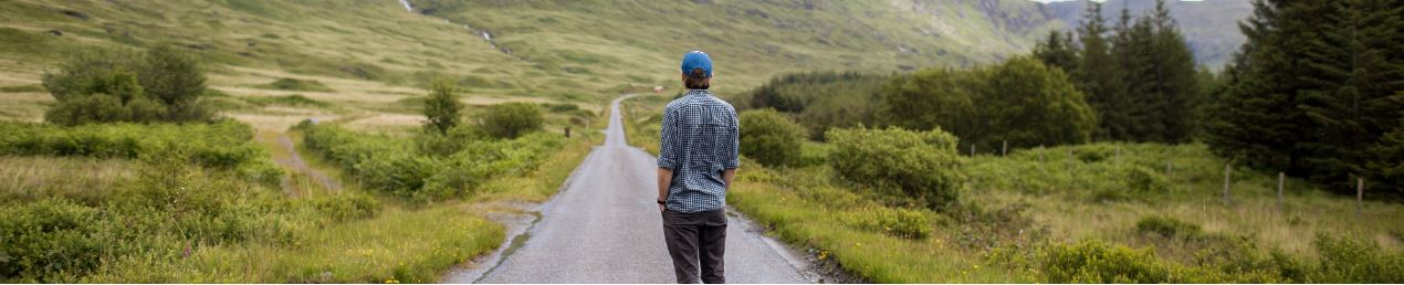 Man looking into distance down road